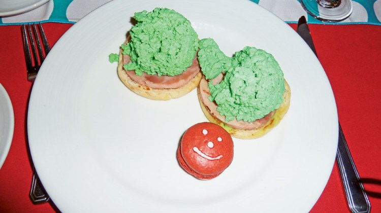 These unnaturally green scrambled eggs are served atop normal pink Canadian bacon and an English muffin half.