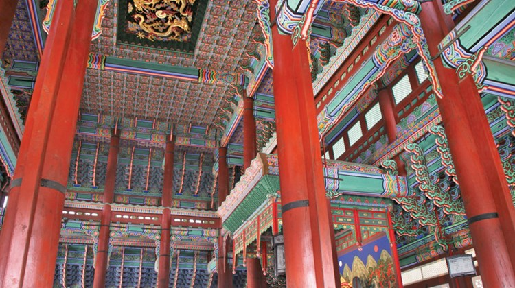 Interior of the king's audience hall at Seoul's Gyeongbok Palace, with brightly painted wood ceiling elements and very red pillars.