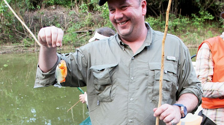 Scott Bahr, vice president of product development and strategic alliances for Marriott Vacations Worldwide, displays a small piranha he caught.