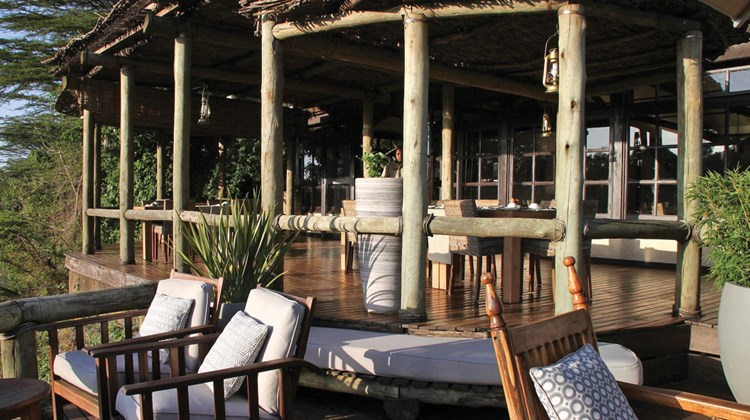 Terrace at Sanctuary Olonana, which accommodates tables for outdoor dining and overlooks the Mara River. The tented camp is located on the Transmara Conservancy abutting the Maasai Mara National Reserve.