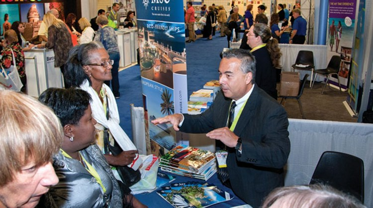 Wayne Peyreau of MSC Cruises chats with delegates on the trade show floor.