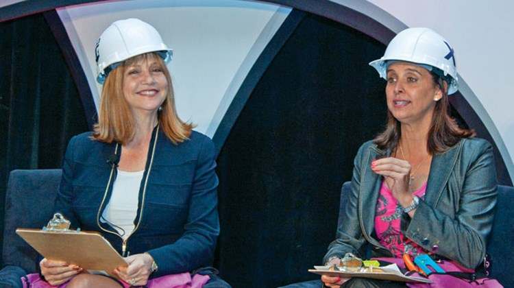 "Royal Caribbean's Vicki Freed, left, and Celebrity's Dondra Ritzenthaler donned hard hats during a keynote presentation titled ""Royal Family of Brands."""