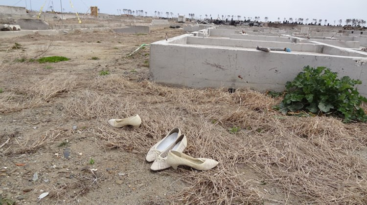 Shoes remain in front of the foundation of a destroyed house. Photo by Johanna Jainchill