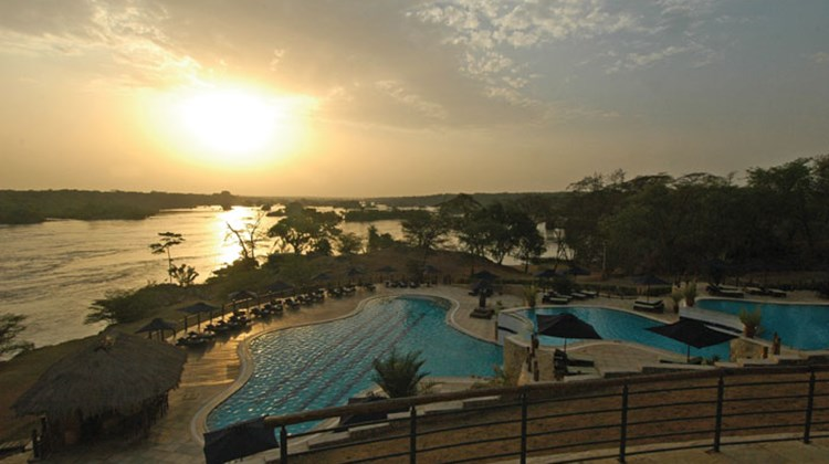 The sun begins to set over the Nile (and swimming pool), seen from the deck of Chobe Safari Lodge in Murchison Falls National Park.
