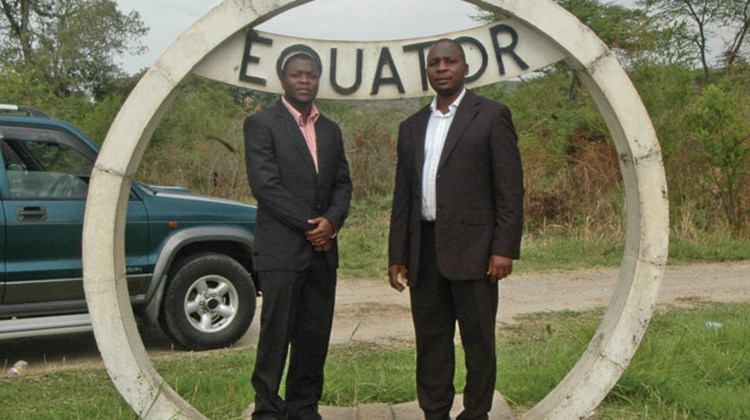 Two Ugandan tourists, one in the Northern Hemisphere and one in the Southern, pose on the equator.